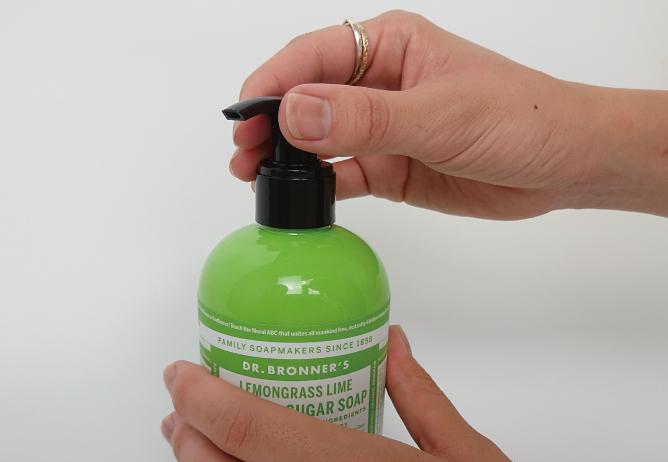 ドクターブロナー オーガニックシュガーソープの開け方、STEP1。ボトルを押さえて、ノズル持つ。